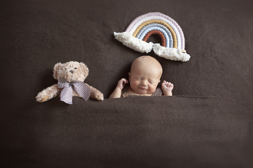Newborn baby boy sleeping on brown blanket with teddy bear tucked in beside him and rainbow prop above him