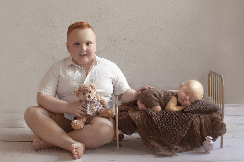Newborn baby boy sleeping in vintage iron bed wearing brown knit romper with brown blanket and layer and pillow with 6 year old sibling sitting beside bed holding teddy bear