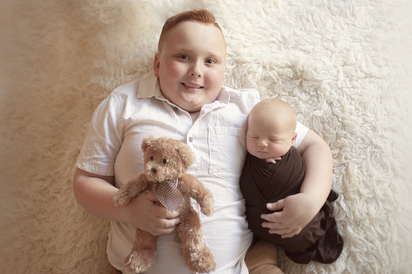 Newborn baby boy sleeping wrapped in brown wrap being held by 6 year old sibling brother on cream fur with teddy bear