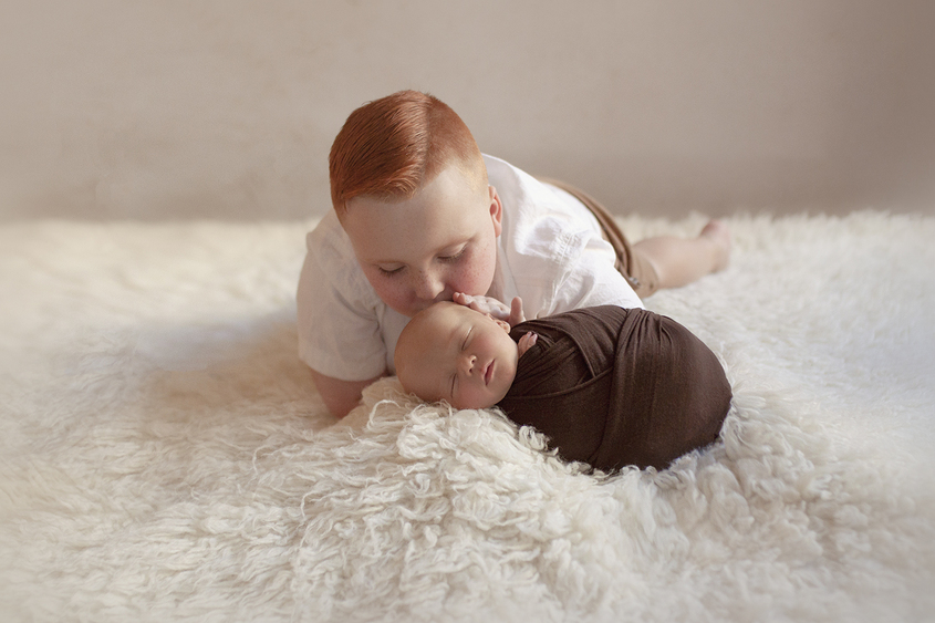 Newborn baby boy sleeping on cream fur wrapped in brown wrap being kissed by 6 year old sibling brother laying beside him