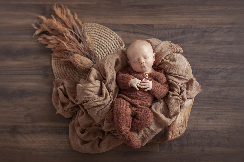 Newborn baby boy sleeping in wooden log bowl wearing rust knit romper with mustard wraps and layers and dried flowers on wooden floor