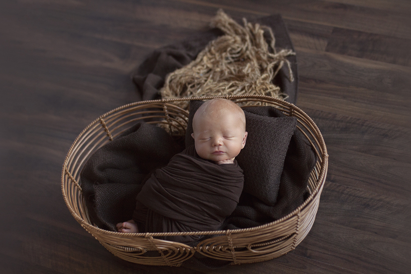 Newborn baby boy sleeping in oval cane basket with brown wrap and blanket and pillow on dark wooden floor and felt brown heart in between toes