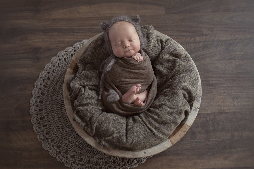 Newborn baby boy sleeping in round wooden bowl with brown blanket and wrap and bear knit bonnet and felt heart and lace layer on wooden floor