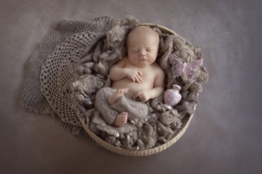 Newborn baby sleeping in oval wooden bowl with brown fluff and wearing brown knit pants on brown backdrop with knit and lace layer and baby girls ashes in an urn