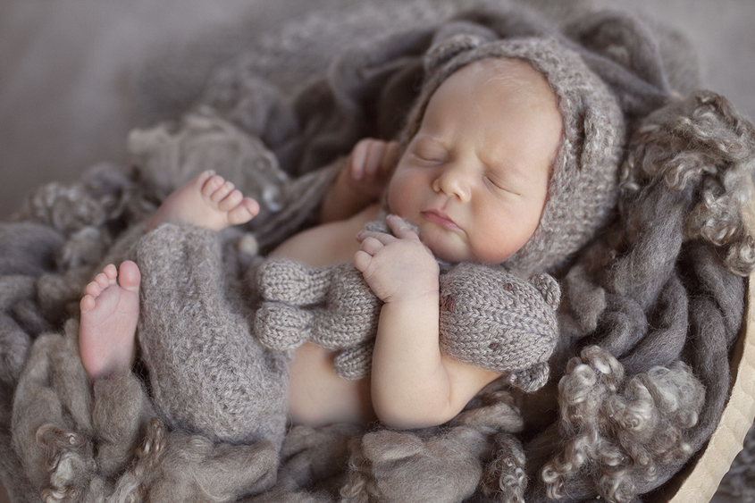 Newborn baby boy sleeping in oval wooden bowl with brown curly felt wearing brown knit pants and knit bear bonnet holding knit bear on brown floor backdrop
