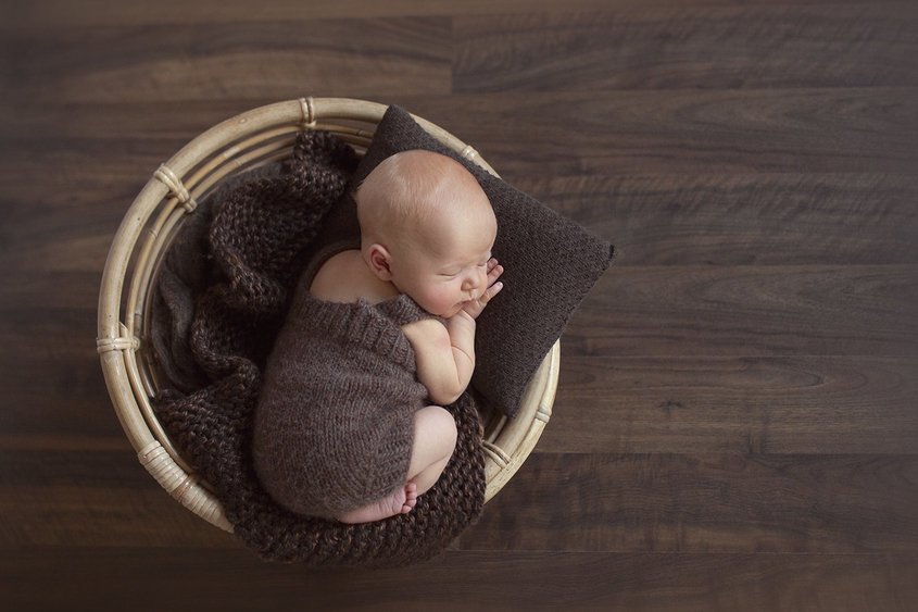 Newborn baby boy sleeping in round papasan chair wearing brown knit overalls with brown knit layer and pillow on wooden floor