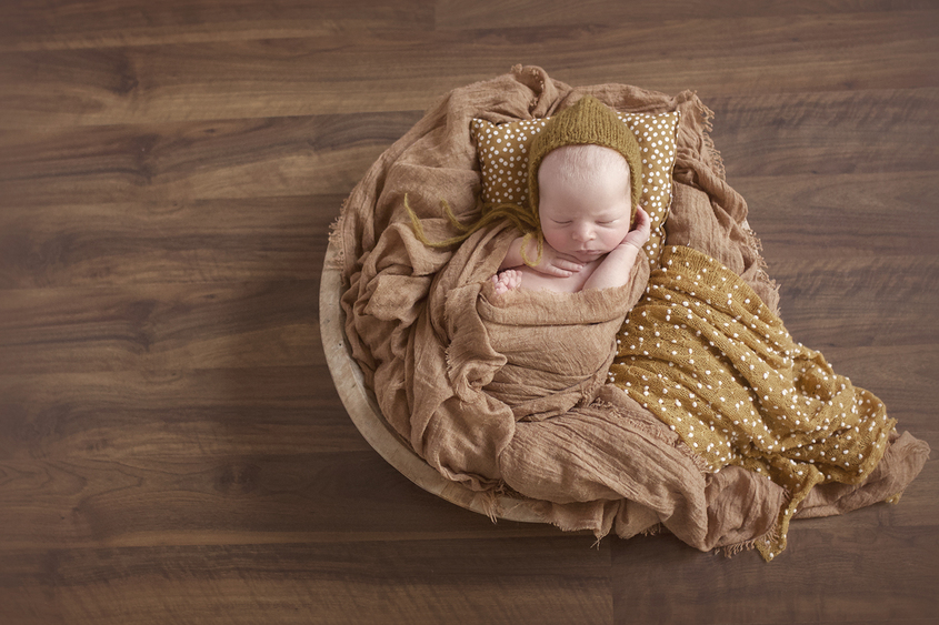 Newborn baby boy sleeping in round wooden bowl with mustard wraps and blankets and pillow on wooden floor