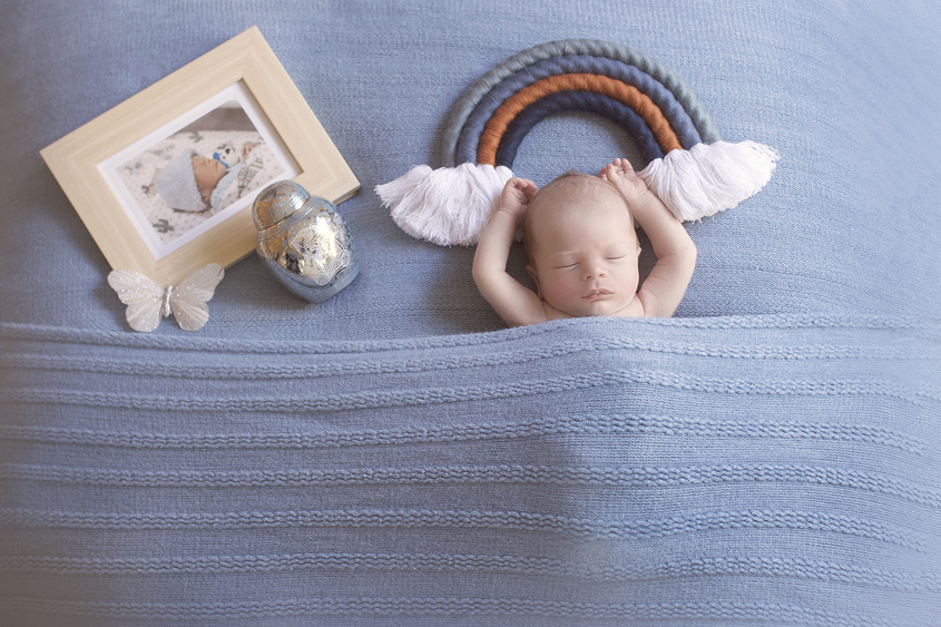 Newborn baby boy sleeping on blue blanket with blue macrame rainbow and frame of premature baby and urn