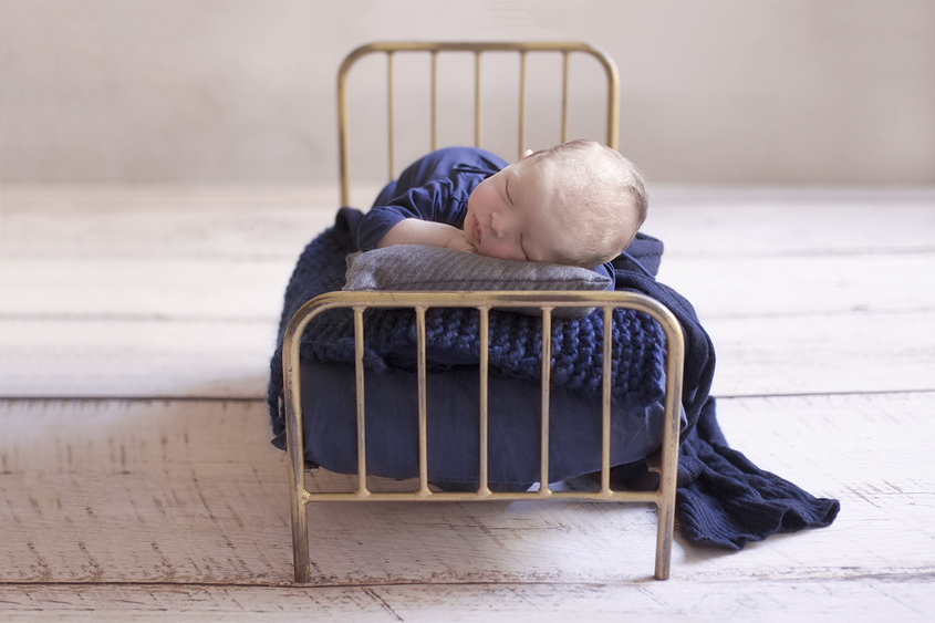 Newborn baby boy sleeping on vintage iron bed with navy blanket and knit layer wearing navy romper on white wooden floor
