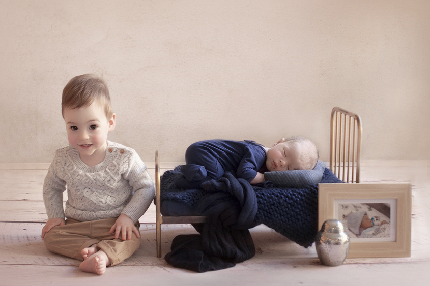 Newborn baby boy sleeping on vintage iron bed with navy blanket and knit layer wearing navy romper on white wooden floor with sibling one year old brother sitting beside him wearing grey knit jumper and tan pants and framed photo of premature baby boy and urn