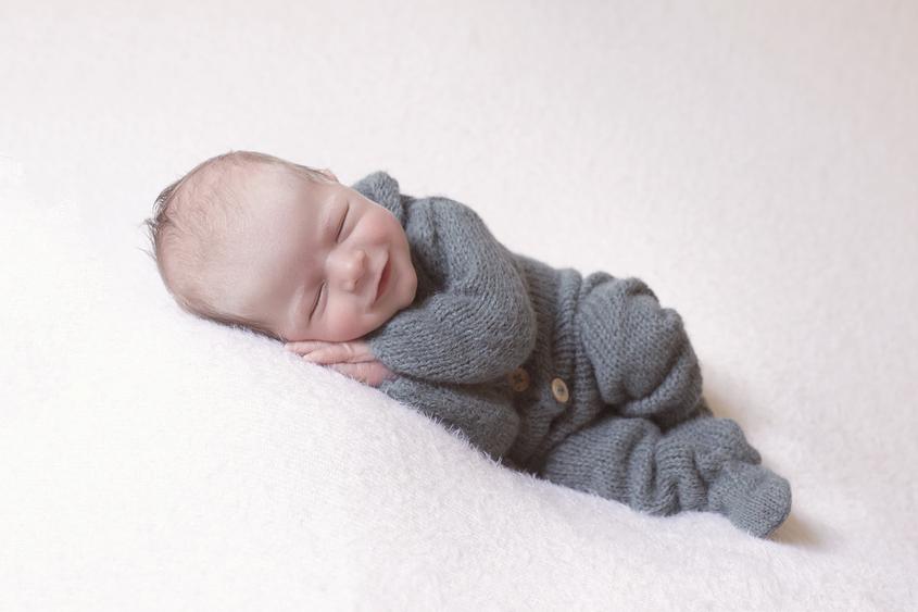 Newborn baby boy sleeping on cream blanket wearing teal knit romper and smiling