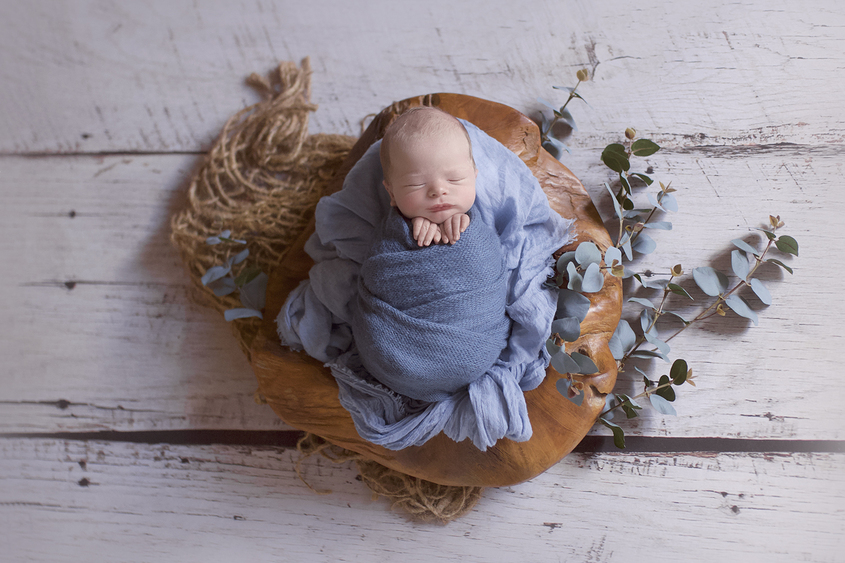 Newborn baby boy sleeping in wooden log bowl with blue wrap and layer with jute layer and green folliage on white wooden floor