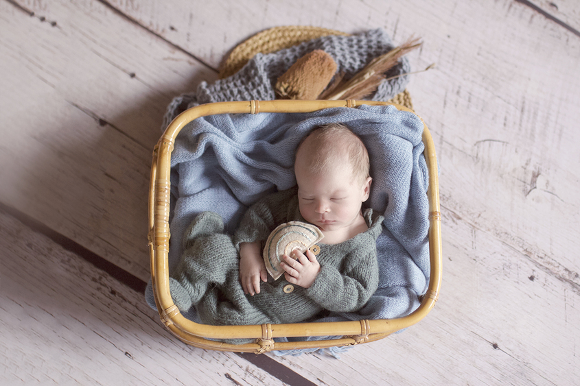 Newborn baby boy sleeping in cane basket wearing teal knit romper with blue blanket and knit layer on white wooden floor with round rattan layer and dried flowers and holding small pastel felt rainbow