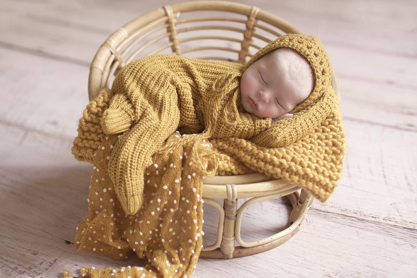 Newborn baby boy sleeping in cane papasan chair with mustard knit layer and romper and bonnet and spotted mustard wrap