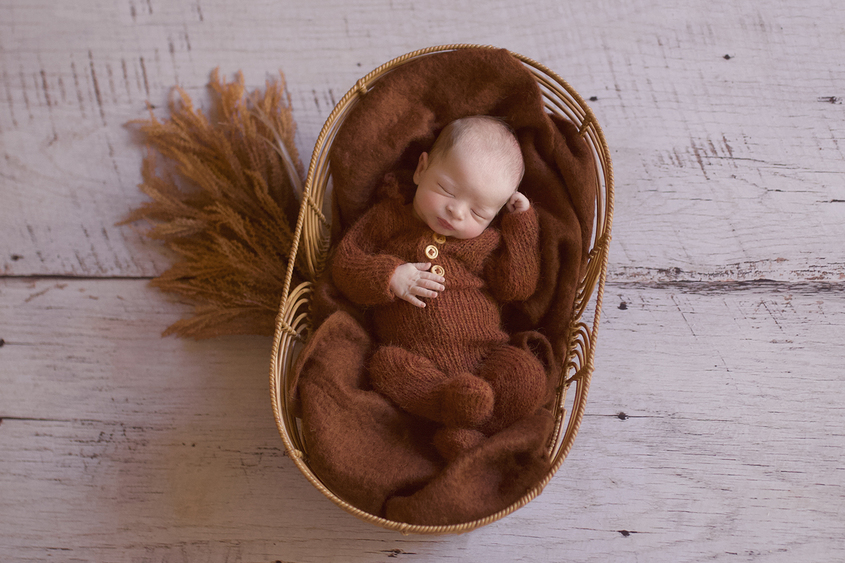 Newborn baby boy sleeping in oval cane basket wearing rust knit romper with rust blanket and dried flowers on white wooden floor
