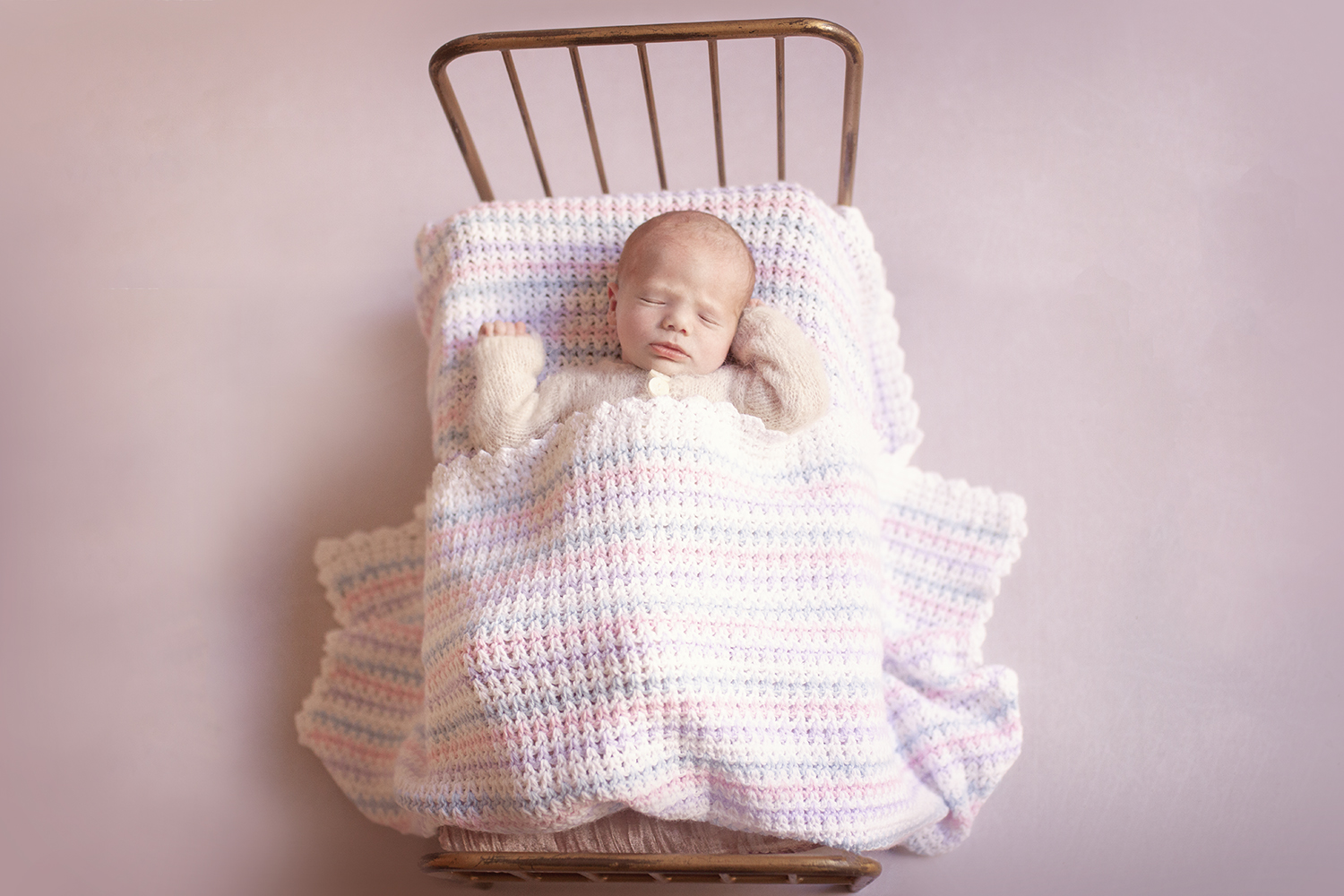 Newborn baby girl sleeping in vintage iron bed with pink white and purple knitted blanket wearing cream knit romper on pink backdrop