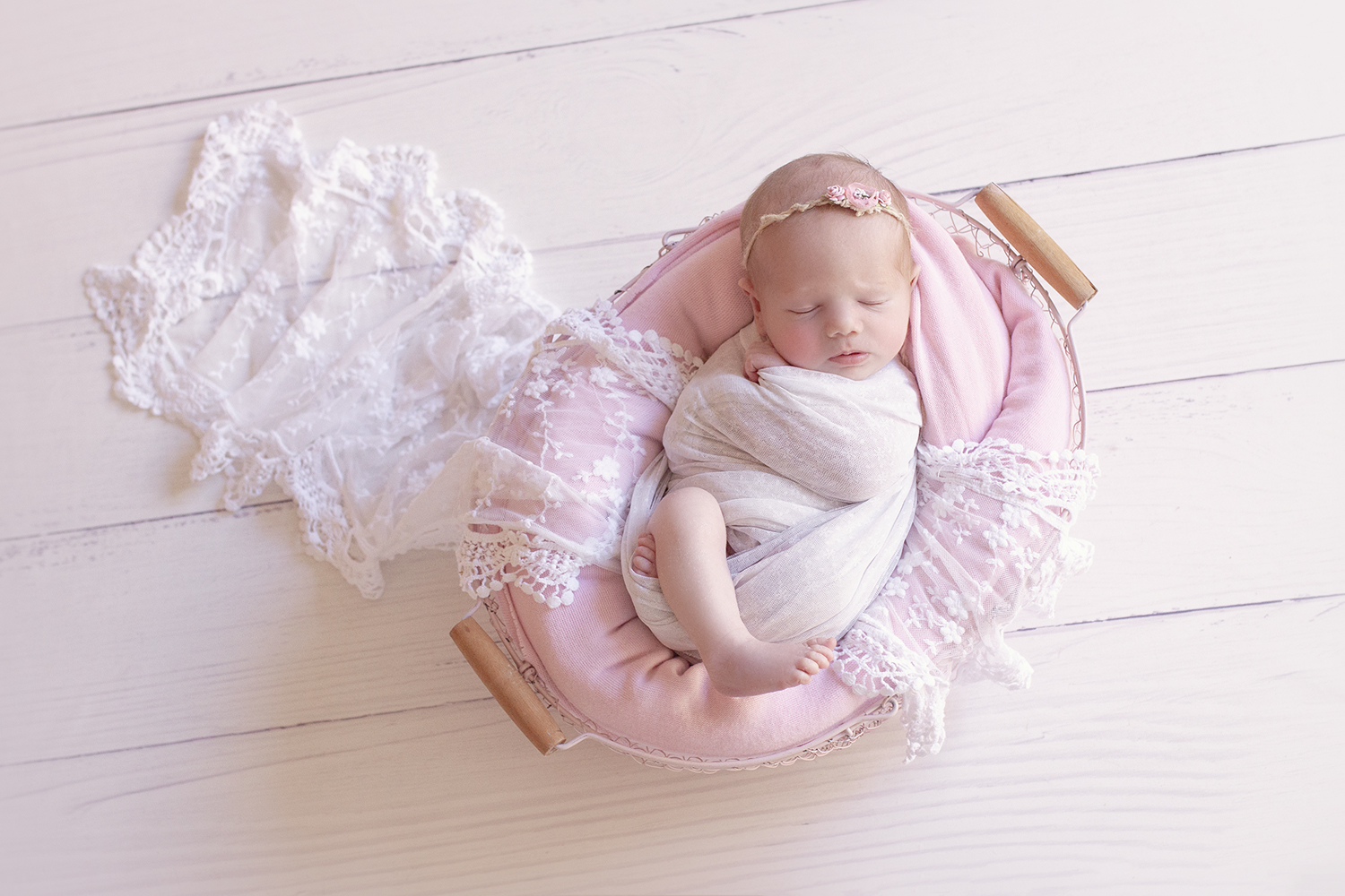 Newborn baby girl in pin farmers basket with pink blanket and white lace wrap wrapped in white wrap with pink flower headband on white wooden floor