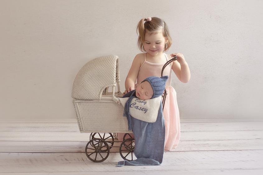 Newborn baby boy sleeping in vintage cane pram with blue wrap and knit bonnet with sibling big sister pushing pram wearing pink dress