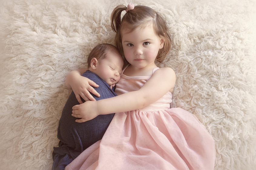 Newborn baby boy wrapped in blue wrap being held by sibling big sister in pink dress laying on cream fur