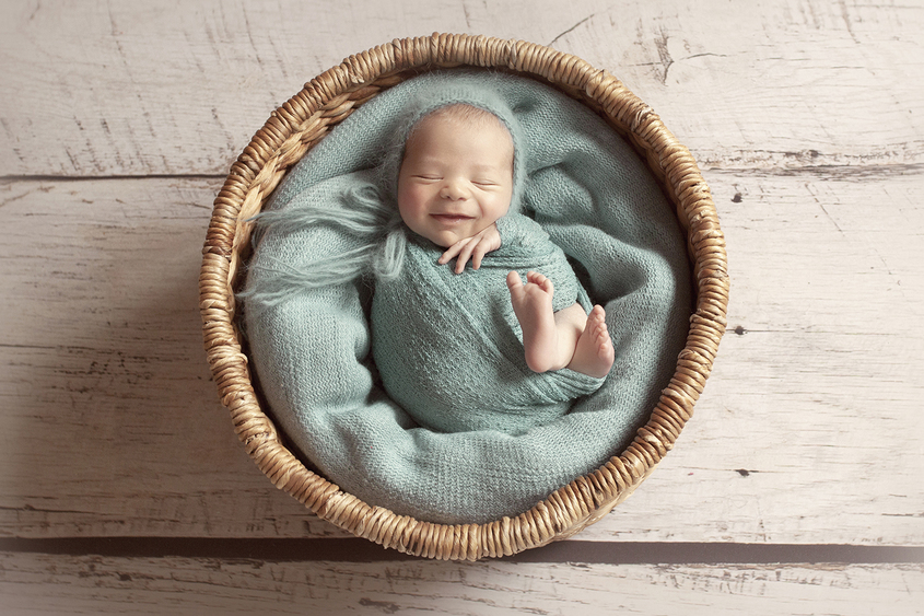 Newborn baby boy sleeping in round cane basket with teal blanket and wrap and knit bonnet on wooden floor