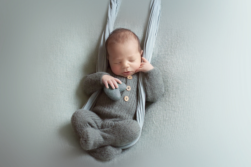 Newborn baby boy sleeping on teal blanket wearing teal knit romper with teal felt heart being support by teal wrap swing