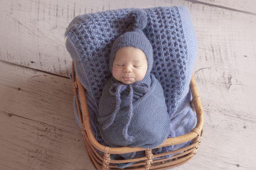 Newborn baby boy sleeping in cane basket with blue wrap and knit beanie and layer on wooden floor