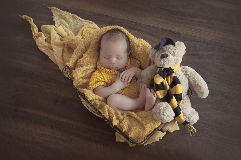Newbon baby boy sleeping in farmer basket with yellow blanket and knit romper and bear on wooden floor