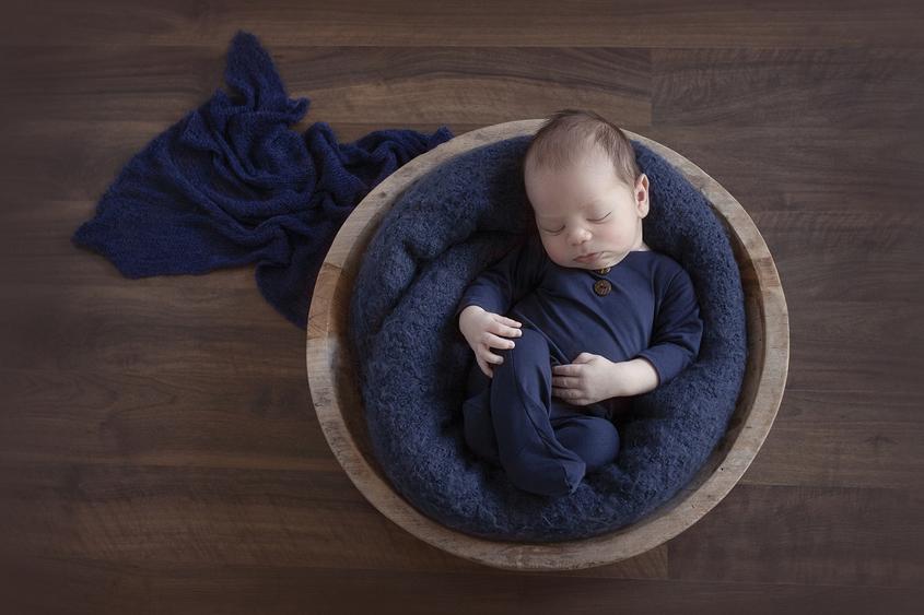 Newborn baby boy sleeping in round wooden bowl wearing navy romper with navy blanket on wooden floor