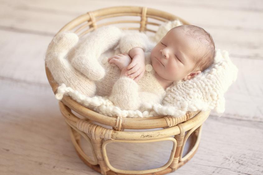 Newborn baby boy sleeping in cane papasan chair wearing cream knit romper with cream knit layer on wooden floor