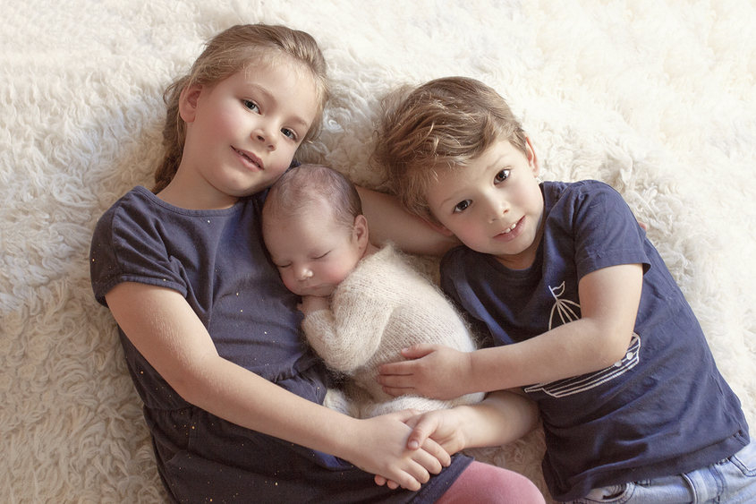 Newborn baby boy sleeping in cream knit romper being held by sibling brother and sister on cream fur