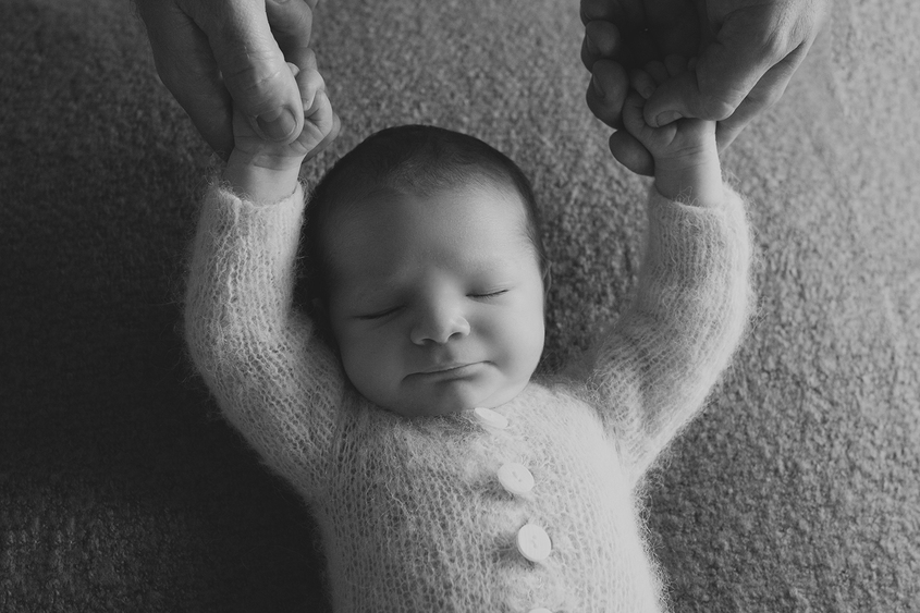 Newborn baby boy wearing cream knit romper sleeping on blanket with hands being held by father in black and white