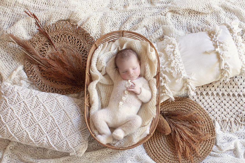 Newborn baby boy sleeping wearing cream knit romper in cane basket surrounded by boho style pillows and throws and dried flowers and hessian mats
