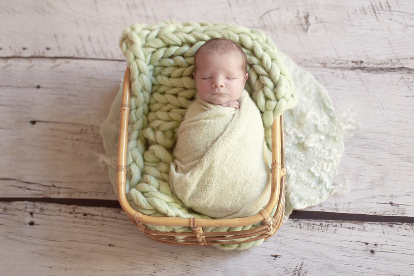 Newborn baby boy sleeping in cane basket wrapped in green wrap with green knit layer and felt on wooden floor