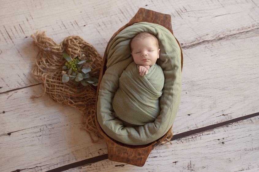 Newborn baby boy sleeping in oval wooden trencher with sage wrap and blanket on wooden floor with hessian layer and folliage holding brown felt heart