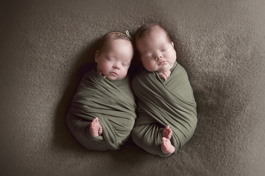 Newborn boy and girl twinssleeping on olive blanket wrapped in olive wraps with girl wearing bow tieback