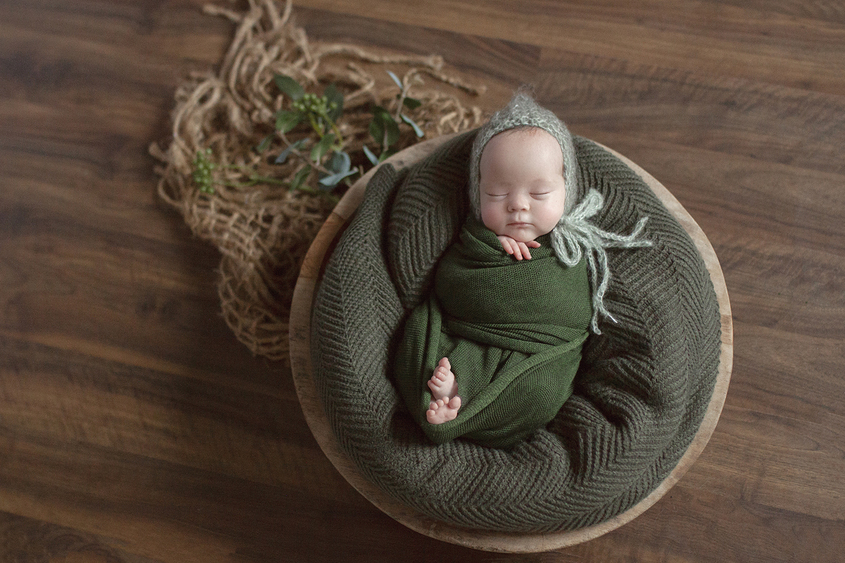 Newborn baby girl sleeping in round wooden bowl with olive wrap and blanket and knit beanie on wooden floor with hessian layer and green folliage
