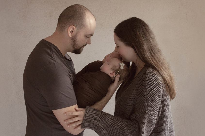 Newborn boy and girl twins wrapped in brown wraps being held by father with mother cuddling in