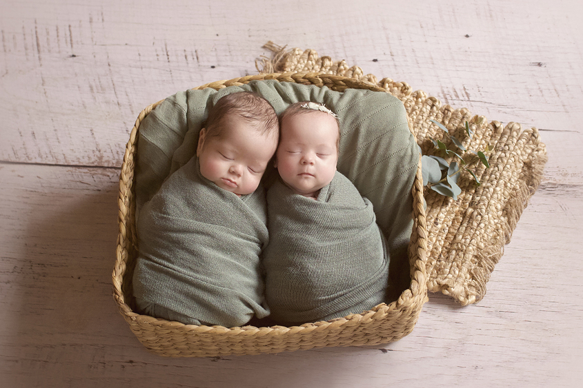 Newborn boy and girl twins sleeping in rectangle cane basket wrapped in green wraps with green blanket and hessian layer with green folliage and boy wearing green knit beanie and girl wearing green bow tieback