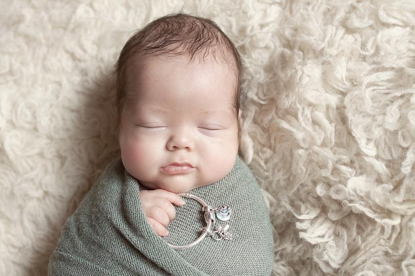 Newborn boy and girl twins sleeping on cream flokati wrapped in green wraps holding pandora bracelets
