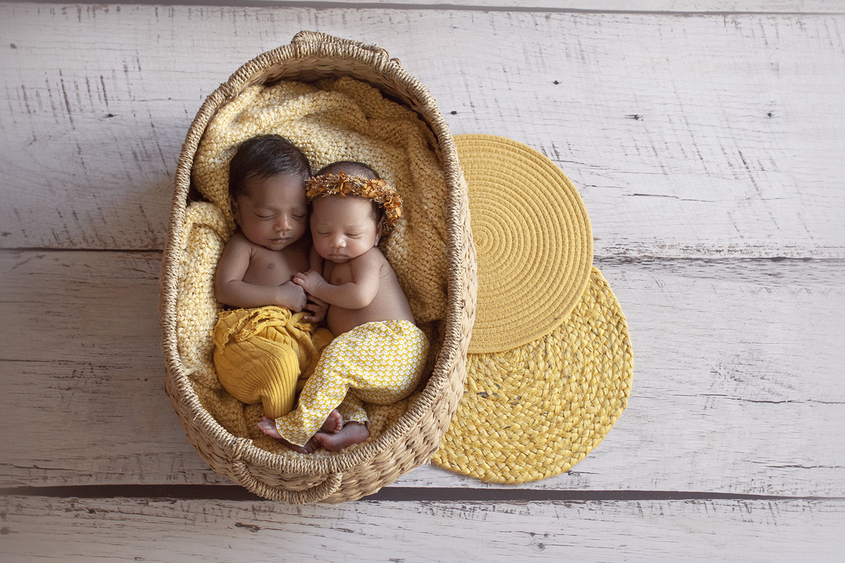 Newborn boy and girl twins sleeping in oval cane basket wearing mustard pants and girl wearing mustard flower crown on white wooden floor with yellow hessian circular layers