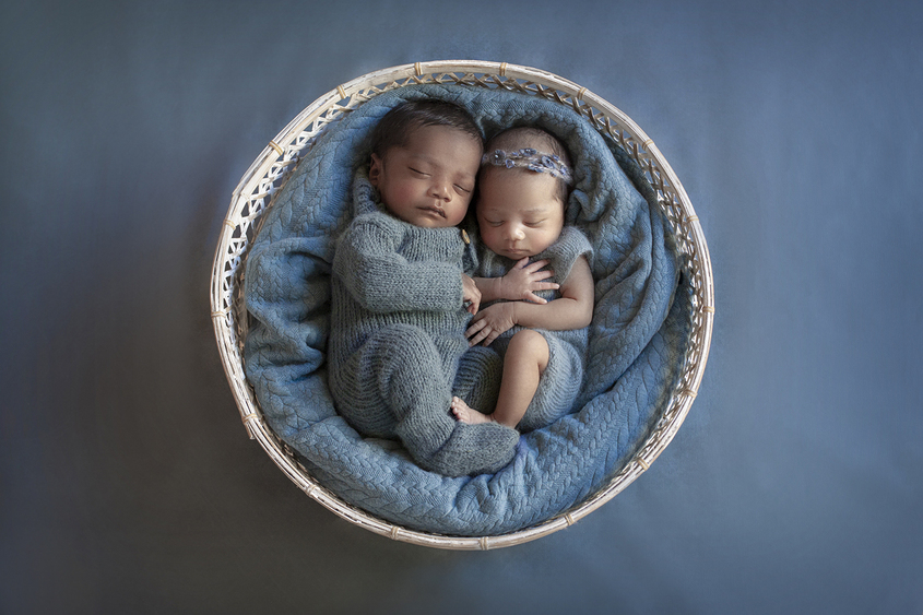 Newborn boy and girl twins sleeping in round white cane basket with blue blanket wearing blue knit rompers and girl wearing blue flower tieback on blue backdrop