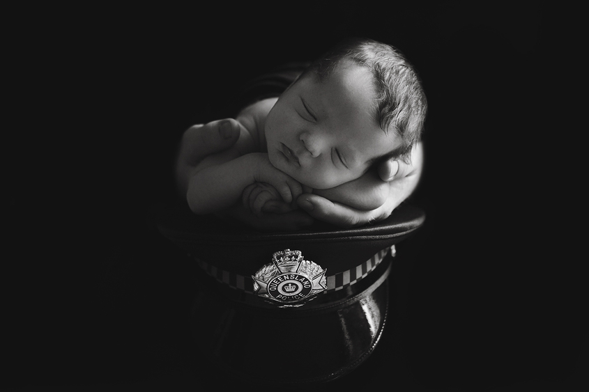 Newborn baby boy being held by fathers hand sitting on top of police hat