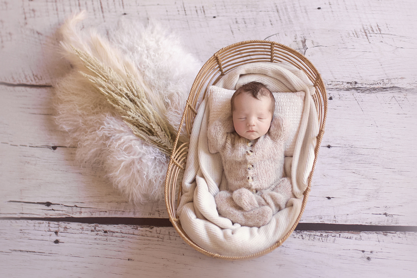 Newborn baby boy sleeping in cane basket wearing cream knit romper with cream blanket and pillow and dried flowers and fur on wooden floor