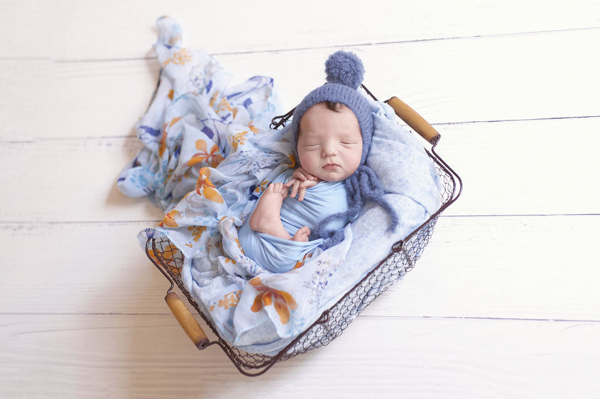 Newborn baby boy sleeping in farmers basket with blue blanket and wrap and knit bonnet with blue floral scarf on white wooden floor