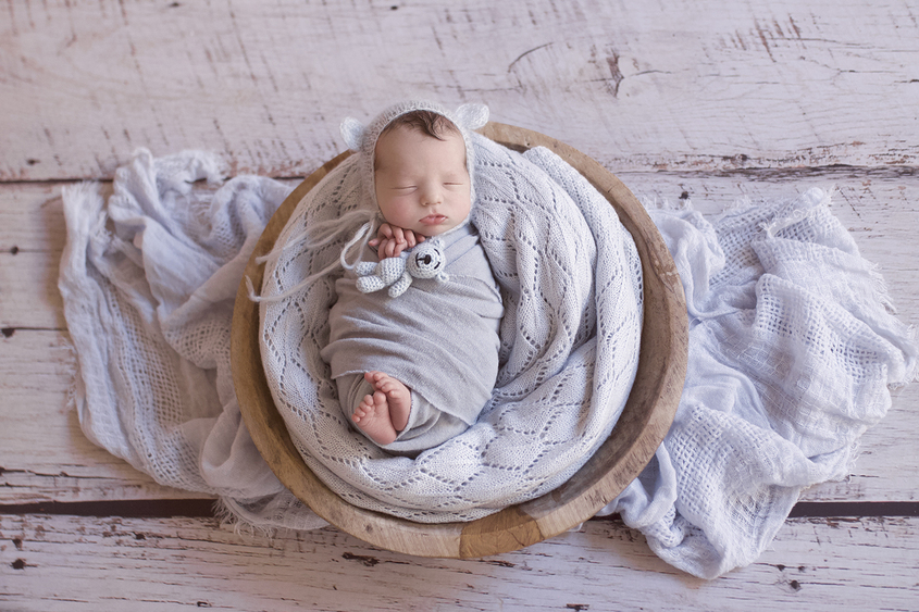 Newborn baby boy sleeping in wooden bowl with blue blanket and wrap and knit bonnet and wrap layer on wooden floor