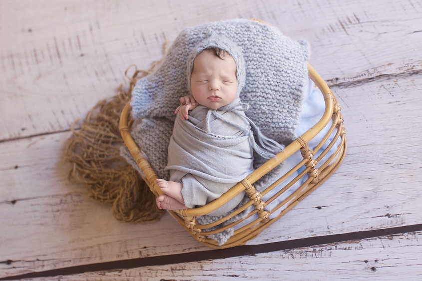 Newborn baby boy sleeping in cane basket with blue wrap and knit layer and hessian layer wearing blue knit beanie on wooden floor