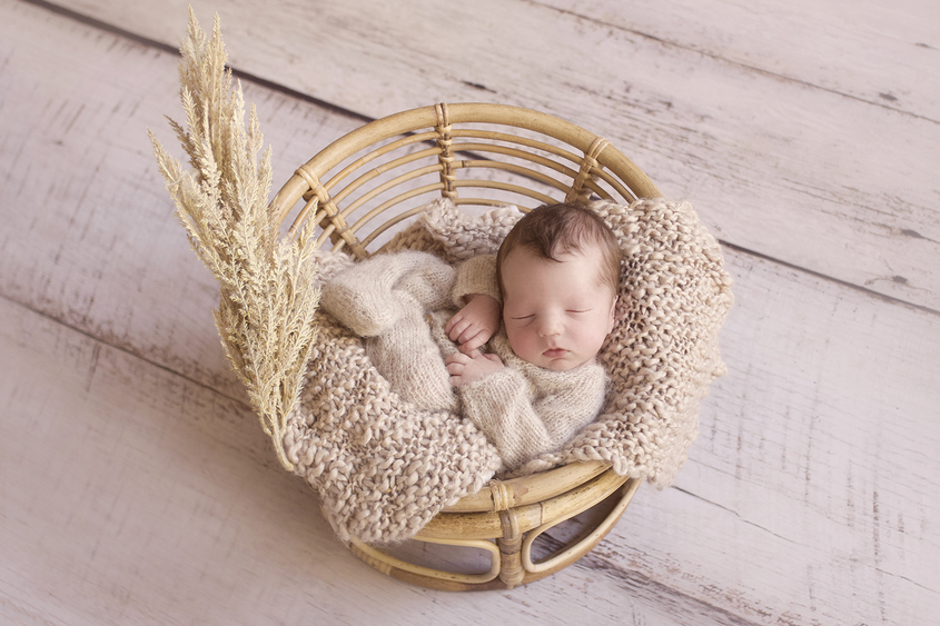 Newborn baby boy sleeping in cane papasan chair wearing cream knit romper with tan knit layer and dried flowers on wooden floor