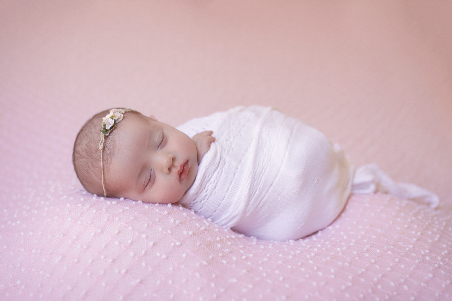 Newborn baby girl sleeping on pink dot blanket wrapped in white wrap with flower tieback