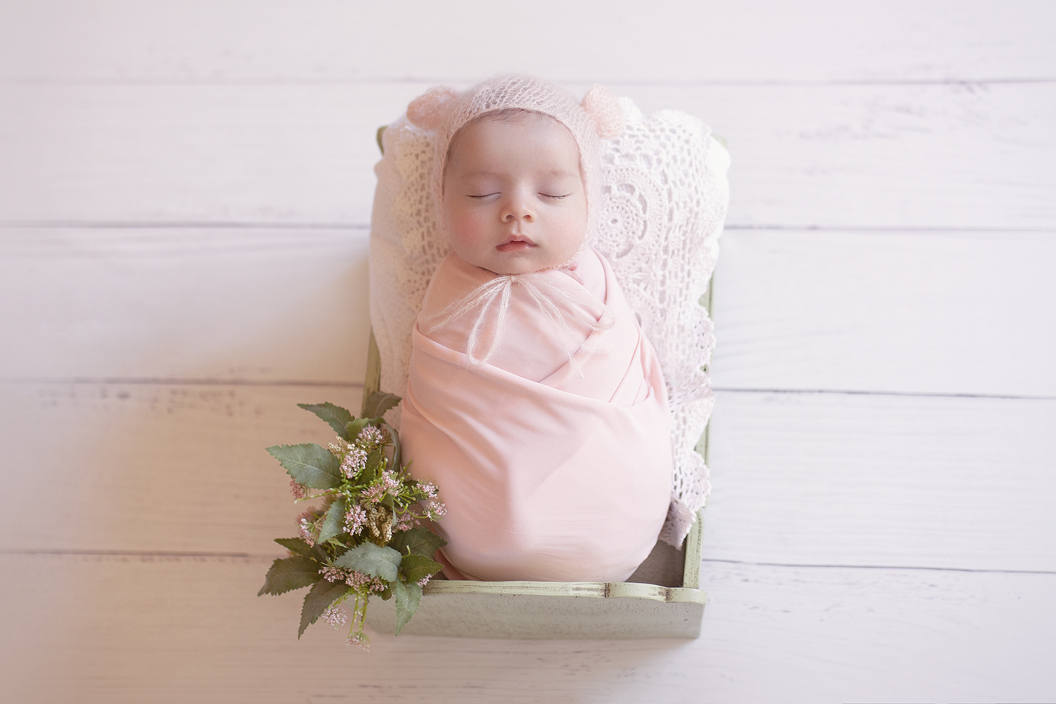 Newborn baby girl sleeping in green wooden bed wrapped in pink wrap with white lace blanket wearing pink knit bear bonnet and pink bunch of flowers on white wooden floor