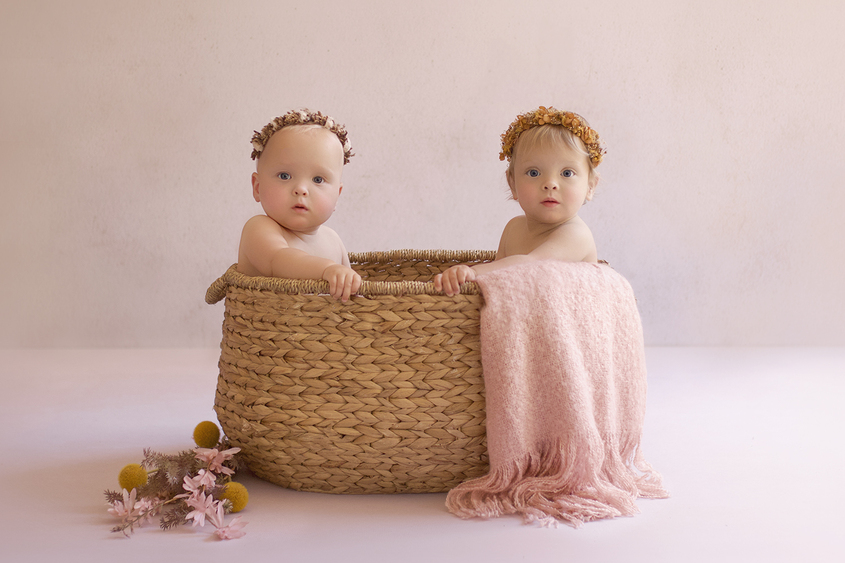 One year old twin girls sitting in cane basket with pink blanket wearing flowers crowns and dried flowers on floor